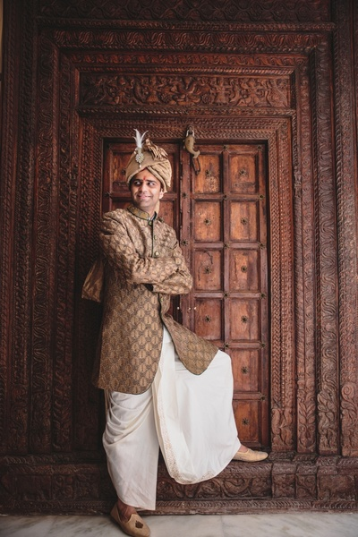 Wearing copper color bandhgala paired with pure white dhoti styled with copper color turban and beige jutti.