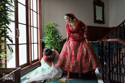 Bridesmaid helps the bride with her footwear in a candid capture