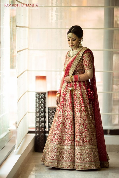 Dressed up in regal red and gold Sabyasachi lehenga styled with royal jewellery and Christian Louboutin bridal shoes for the wedding day!