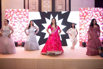a candid capture of the bride and her bridesmaids dancing at the sangeet