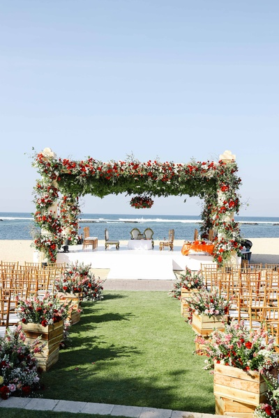 A mandap by the seaside, bedecked in white and red flowers.