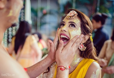 the groom smearing haldi on the bride's face