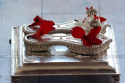 Silver Padukas adorned with red and white Champa flowers