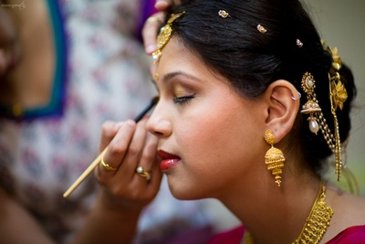 Bridal hairstyle adorned by juda and hair ornaments enhanced by gold eye shadow and red glossy lipstick