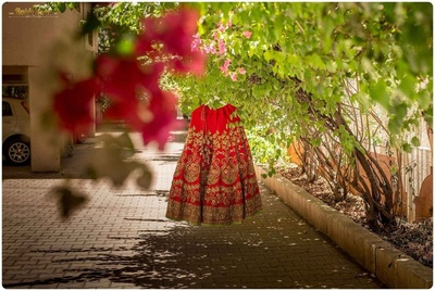 Red wedding lehenga heavily embellished with sequins, zari motifs, stones and beads