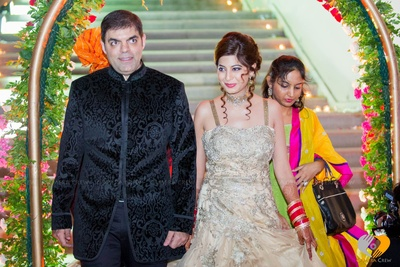 Groom glamorously dressed in smoky  black self textured bandhgala sherwani