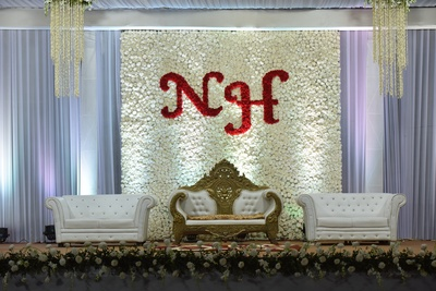For the reception, the stage backdrop was decorated with white roses with the couple's initials featuring in red roses.
