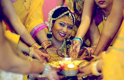 Bride stained in yellow wearing a floral maathapatti for her Haldi ceremony
