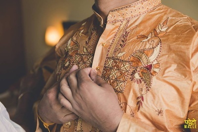 Dressed in a golden beige silk kurta with detailed intricate dori work for the wedding day.