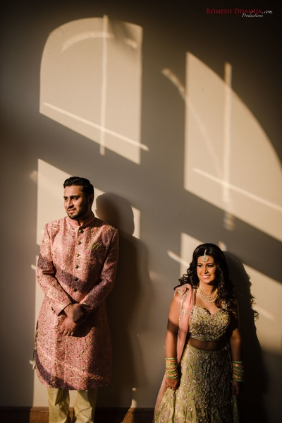 candid couple shot in their sangeet outfits