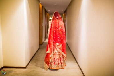 Orange and red wedding lehenga, styled with red bridal dupatta embellished with buttis and gold beads lace