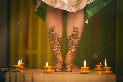 Bride's feet covered in intricately patterned mehendi design, shot with diyas around