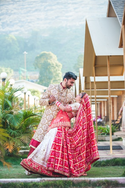 the bride and groom posing romantically against a beautiful backdrop