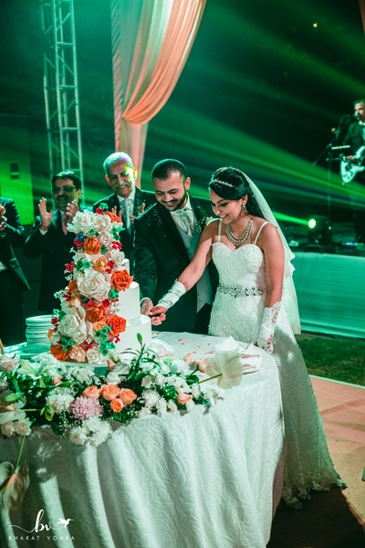 The bride and groom cutting their delectable white and floral cutting cake.