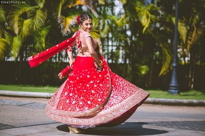 Twirling bride in Red and golden sabyasachi