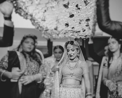 Gorgeous bride walking under the floral chaadar