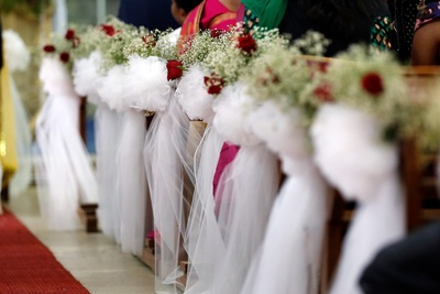 Church decorated with white sheer clustered drapes and floral tie backs