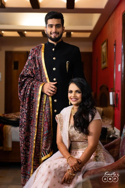 The groom looks debonair in a black achkan, while the bride flaunts a baby pink and gold lehenga.