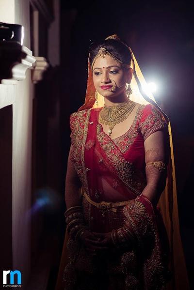 Red wedding lehenga embellished with gold jewellery set, chunky kamarband, and bajuband