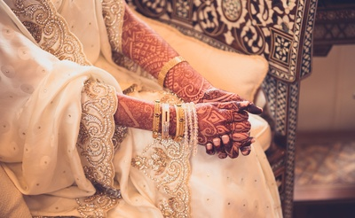 The bride pairs up gold kadas and pearl bracelets with her ensemble!