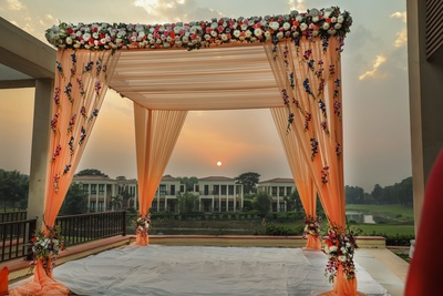 A rustic light orange mandap covered in ferns and foliage, set up against a beuatiful view!