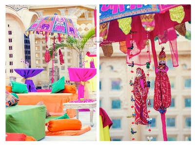Colorful seating arrangements and hanging rajasthani dolls for the mehendi ceremony decor.