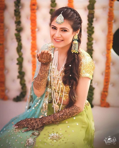 quirky bride showing off her hand mehndi design and beautiful braided hairstyle