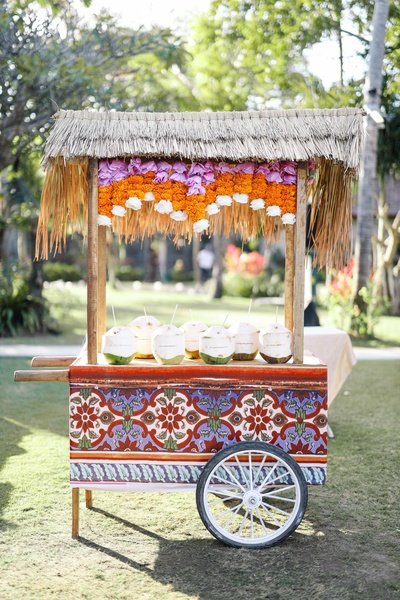 A cart displaying coconuts with the name of the couple engraved on them.
