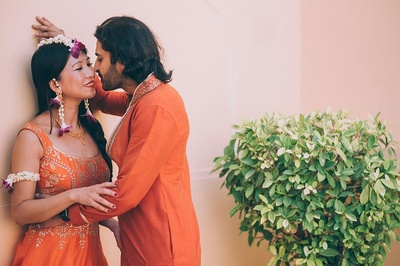 Bride and groom wearing saffron indian outfits for their mehendi ceremony held at Samode Palace, Jaipur