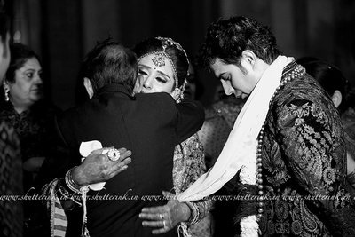 Bidding a goodbye to her loved ones, the bride embraces her father with a warm hug