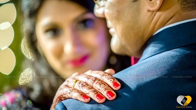 Gold wedding band adorned with red manicure nails