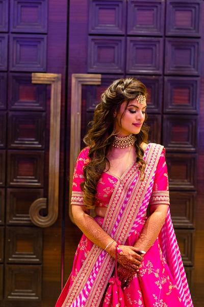 the bride in fuschia pink Sabyasachi lehenga for her sangeet