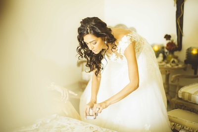 The bride wearing a splendid white gown getting ready for her wedding