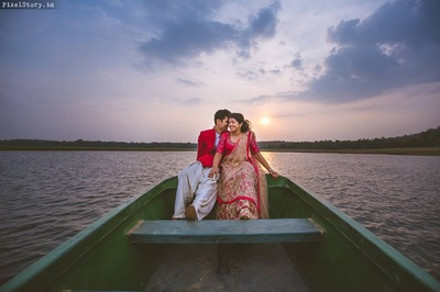Couple posing on a boat in between the lake for their pre wedding shoot captured beautifully by PixelStory.in.