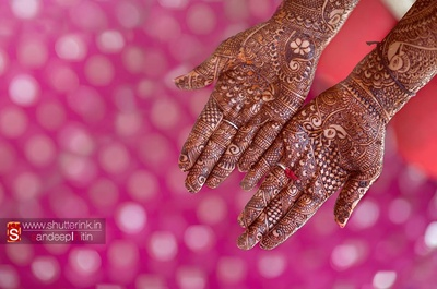 Bride's arms covered in elaborate, knotted mehendi designs