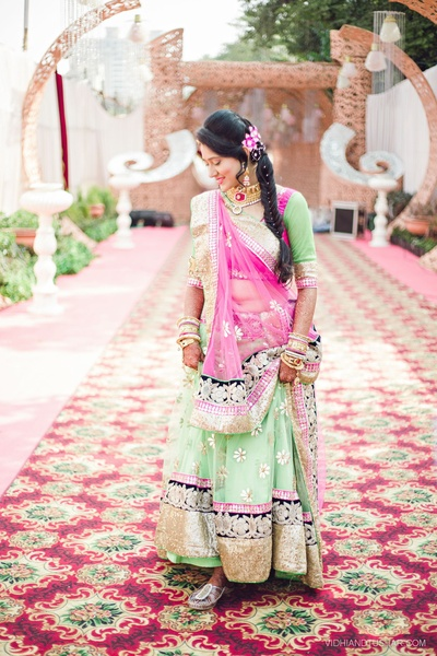 Mint and pink lehenga featuring embellished thread work, gold shimmer border and buttis