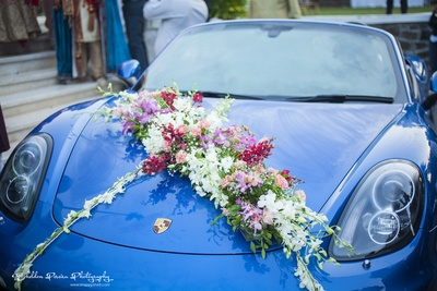 Couple send off car adorned with ferns and white, pink, magenta flowers