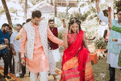 the bride and groom being showered  with flowers as they enter the mehendi ceremony