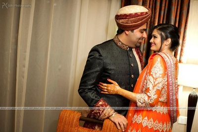Tangerine layered anarkali lehenga featuring patchwork, detailed emboidery and stone work. Groom dressed in black textured bandhgala sherwani with a maroon and gold Safa and Dushala