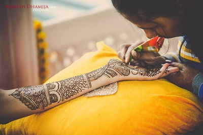 Hand covered with intricate bridal mehendi designs.