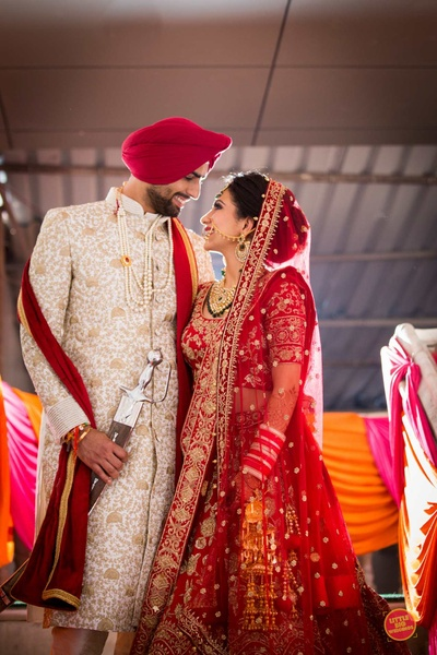 The bride and the groom posing in a red lehenga and ivory sherwani
