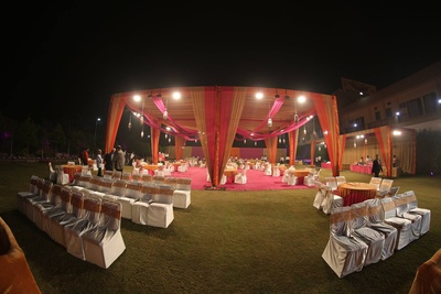 Outdoor wedding venue decorated with drapes, suspended light lamps, and table setup