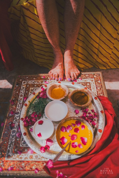 Authentic haldi setup with a meenakari table, haldi, milk and chandan paste
