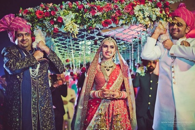 Bride entry under a flower chadar