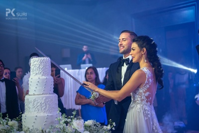 The couple cutting their 4-tiered cake at the wedding reception.