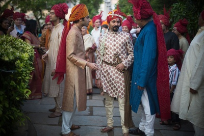 Groom dressed in an ivory sherwani featuring bronze woven details all over