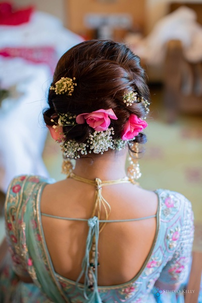 Gorgeous bridal bun with baby breaths and pink roses.