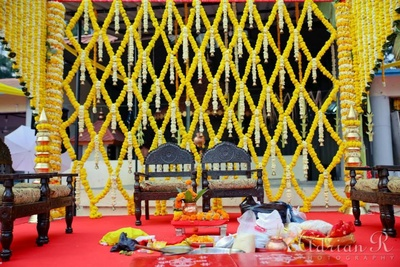 Vedi Mandap decorated with yellow Marigold geometrical arrangement adorned with bell drops
