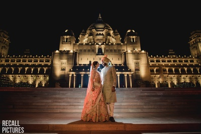 Bride and groom posing against a royal backdrop on their wedding day