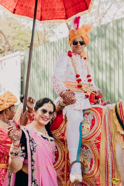the groom posing with his mother while the baraat proceeds